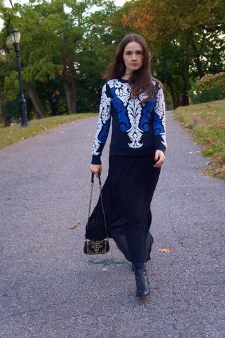 Как и с чем носить: бело-темно-синий свитер с круглым вырезом с вышивкой, черная длинная юбка со складками, черные кожаные ботильоны, черная кожаная сумка через плечо с шипами