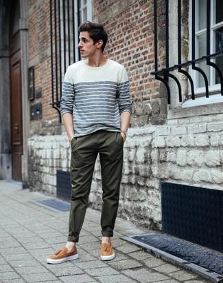 Темно-зеленые брюки чинос: с чем носить и как сочетать: Фанатам стиля кэжуал понравится тандем бело-темно-синей футболки с длинным рукавом в горизонтальную полоску и темно-зеленых брюк чинос. Очень неплохо здесь будут смотреться светло-коричневые кожаные слипоны.