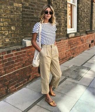 Как и с чем носить: бело-темно-синяя футболка с круглым вырезом в горизонтальную полоску, бежевые брюки-кюлоты, золотые кожаные сандалии на плоской подошве, черные солнцезащитные очки