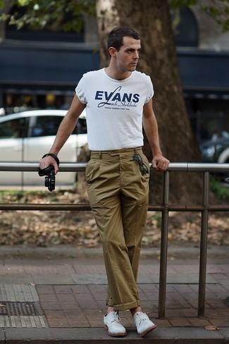 Белые замшевые туфли дерби: с чем носить и как сочетать: Бело-темно-синяя футболка с круглым вырезом с принтом и оливковые брюки чинос будет отличным вариантом для простого повседневного лука. Думаешь привнести сюда нотку классики? Тогда в качестве обуви к этому луку, обрати внимание на белые замшевые туфли дерби.
