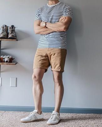С чем носить белые кожаные низкие кеды мужчине: Для активного дня в компании друзей прекрасно подходит сочетание бело-темно-синей футболки с круглым вырезом в горизонтальную полоску и светло-коричневых шорт. Вкупе с этим ансамблем органично будут выглядеть белые кожаные низкие кеды.