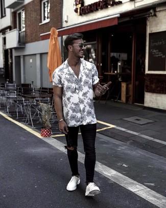 Как и с чем носить: бело-черная рубашка с коротким рукавом с цветочным принтом, черные рваные зауженные джинсы, белые кожаные туфли дерби