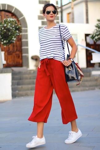 Как и с чем носить: бело-черная футболка с круглым вырезом в горизонтальную полоску, красные брюки-кюлоты, белые кожаные низкие кеды, темно-синяя кожаная большая сумка