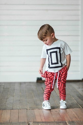 Как и с чем носить: бело-черная футболка с принтом, красные спортивные штаны, белые кеды