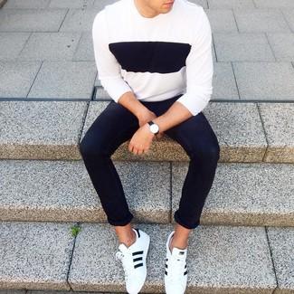 Как и с чем носить: бело-черный свитер с круглым вырезом, черные зауженные джинсы, бело-черные кожаные низкие кеды, черные кожаные часы