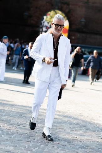 Как и с чем носить: белый двубортный пиджак, черная футболка-поло, белые классические брюки, черно-белые кожаные классические ботинки