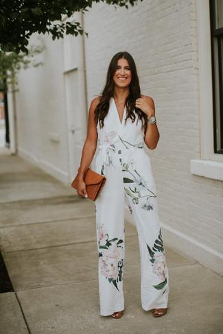 Женские луки: Белый комбинезон с цветочным принтом — хороший вариант для дам, которые никогда не сидят на месте. В сочетании с этим ансамблем наиболее удачно выглядят коричневые кожаные босоножки на каблуке.