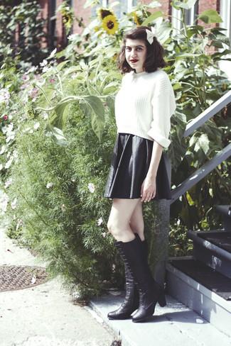 Как и с чем носить: белый вязаный короткий свитер, черная кожаная короткая юбка-солнце, черные кожаные сапоги, белый галстук-бабочка