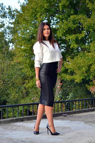 Белый короткий свитер и черная кожаная юбка-миди — хороший вариант для прогулки с друзьями или похода по магазинам. Если ты не боишься сочетать в своих луках разные стили, на ноги можно надеть черные кожаные туфли.