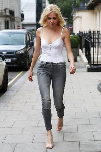С чем носить прозрачные резиновые босоножки на каблуке: Сочетание белого корсета и серых рваных джинсов скинни - самый простой из возможных образов для активного уикенда. В этот ансамбль очень просто интегрировать прозрачные резиновые босоножки на каблуке.
