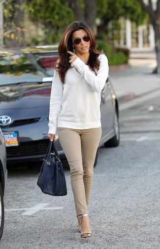 Как и с чем носить: белый свитер с v-образным вырезом, бежевые джинсы скинни, серебряные кожаные босоножки на каблуке, черная кожаная большая сумка