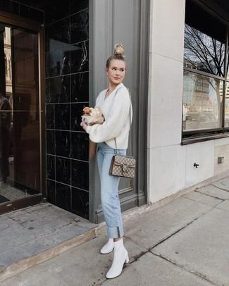 Как и с чем носить: белый свитер с v-образным вырезом, голубые джинсы, белые кожаные ботильоны, бежевая сумка-саквояж из плотной ткани с принтом