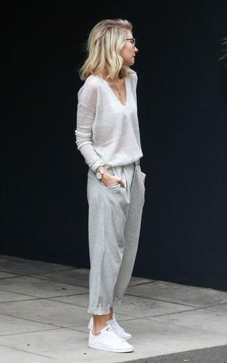 Как и с чем носить: белый свитер с v-образным вырезом, серые брюки-галифе, белые низкие кеды, золотые часы