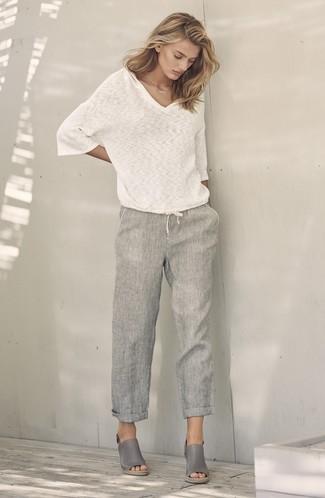 Как и с чем носить: белый свитер с v-образным вырезом, серые льняные широкие брюки, серые кожаные босоножки на танкетке
