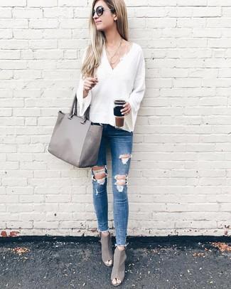 Как и с чем носить: белый свитер с v-образным вырезом, синие рваные джинсы скинни, серые кожаные ботильоны с вырезом, серая кожаная большая сумка