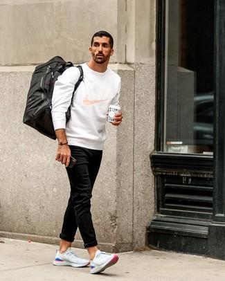 Как и с чем носить: белый свитшот с принтом, черные джинсы, белые кроссовки, черная дорожная сумка из плотной ткани