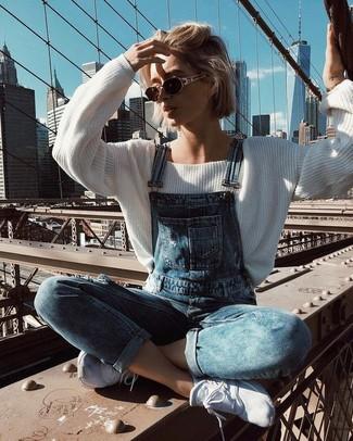Как и с чем носить: белый свободный свитер, синие джинсовые штаны-комбинезон, белые кроссовки, темно-коричневые солнцезащитные очки