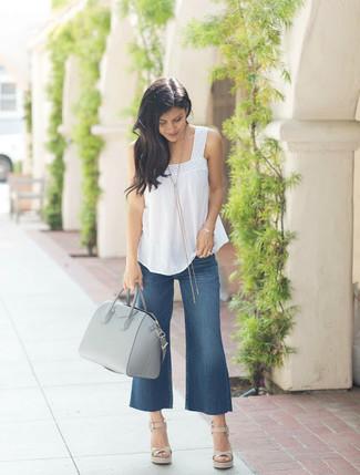 Темно-синие джинсовые брюки-кюлоты: с чем носить и как сочетать: Стильное сочетание белого топа без рукавов и темно-синих джинсовых брюк-кюлотов поможет выразить твой оригинальный личный стиль и выгодно выделиться из общей массы. Такой наряд легко получает свежее прочтение в тандеме с бежевыми кожаными босоножками на танкетке.