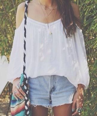Как и с чем носить: белый топ с открытыми плечами, голубые джинсовые шорты, разноцветная сумка через плечо из плотной ткани, золотое колье