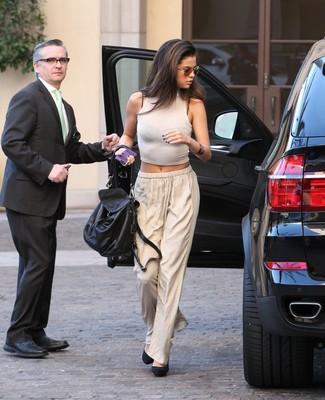 Как Selena Gomez носит Белый укороченный топ, Бежевые широкие брюки, Черные замшевые туфли, Черная кожаная сумка-саквояж