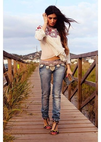 Как и с чем носить: белая блуза-крестьянка с вышивкой, синие джинсы, разноцветные замшевые босоножки на каблуке, черный кожаный клатч с принтом