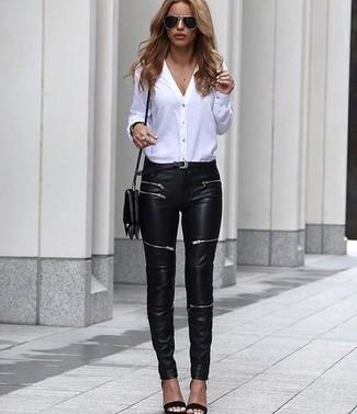 Как и с чем носить: белая блуза на пуговицах, черные кожаные джинсы скинни, черные кожаные босоножки на каблуке, черная кожаная сумка через плечо
