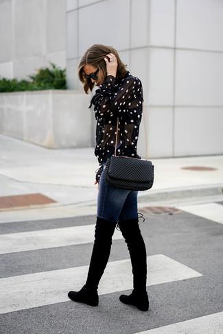 Как и с чем носить: черно-белая блуза на пуговицах в горошек, темно-синие джинсы скинни, черные замшевые ботфорты, черная кожаная стеганая сумка через плечо