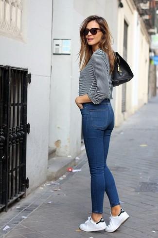 Как и с чем носить: бело-черная блуза на пуговицах в вертикальную полоску, синие джинсы скинни, белые низкие кеды из плотной ткани, черная кожаная сумка-саквояж
