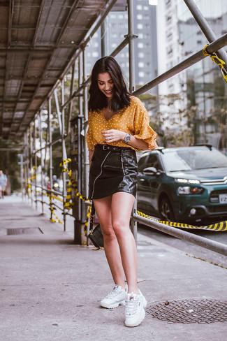 Как и с чем носить: горчичная блуза с коротким рукавом в горошек, черная кожаная мини-юбка, белые кроссовки, черная кожаная сумка-саквояж