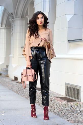 Как и с чем носить: бежевая блузка с длинным рукавом с рюшами, черные кожаные брюки-галифе, темно-красные замшевые босоножки на каблуке, розовая кожаная сумка через плечо