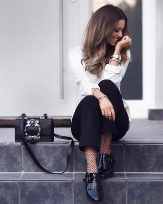 Как и с чем носить: белая блузка с длинным рукавом, черные брюки-галифе, черные кожаные лоферы c бахромой, черная кожаная сумка через плечо с украшением