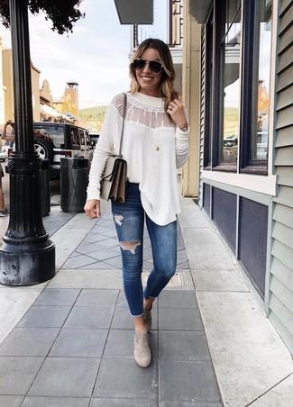 Как и с чем носить: белая кружевная блузка с длинным рукавом, темно-синие рваные джинсы скинни, серые замшевые ботильоны, коричневая кожаная сумка через плечо