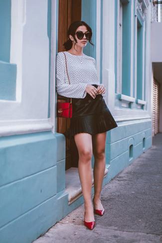 Как и с чем носить: бело-черная блузка с длинным рукавом в горошек, черная кожаная мини-юбка со складками, красные кожаные туфли, красная кожаная сумка через плечо