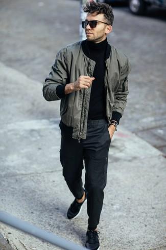 Темно-серые брюки чинос: с чем носить и как сочетать: Темно-зеленый бомбер и темно-серые брюки чинос — обязательные элементы в гардеробе любителей расслабленного стиля. Создать модный контраст с остальными составляющими этого лука помогут черные низкие кеды.