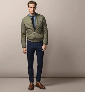 Как и с чем носить: оливковый бомбер, голубая классическая рубашка из шамбре, темно-синие брюки чинос, коричневые кожаные монки с двумя ремешками