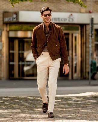 Коричневый замшевый бомбер: с чем носить и как сочетать мужчине: Коричневый замшевый бомбер в сочетании с белыми брюками чинос продолжает импонировать стильным джентльменам. Любители экспериментировать могут закончить лук темно-коричневыми кожаными лоферами, тем самым добавив в него чуточку строгости.