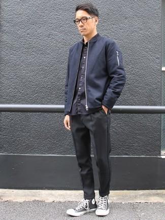 Черные брюки чинос: с чем носить и как сочетать: Сочетание темно-синего бомбера и черных брюк чинос — отличная идея для создания мужского лука в стиле элегантной повседневности. Почему бы не привнести в этот ансамбль толику непринужденности с помощью черно-белых высоких кед из плотной ткани?