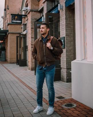 Как и с чем носить: темно-коричневый замшевый бомбер, темно-сине-белая рубашка с длинным рукавом в горошек, синие джинсы, белые низкие кеды