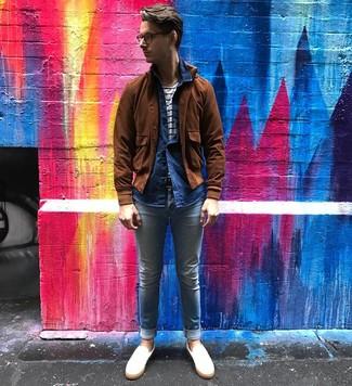 Коричневый замшевый бомбер: с чем носить и как сочетать мужчине: Несмотря на то, что это достаточно простой ансамбль, тандем коричневого замшевого бомбера и голубых зауженных джинсов неизменно нравится стильным мужчинам, неизбежно покоряя при этом сердца противоположного пола. Любители экспериментировать могут завершить лук белыми кожаными слипонами, тем самым добавив в него толику классики.
