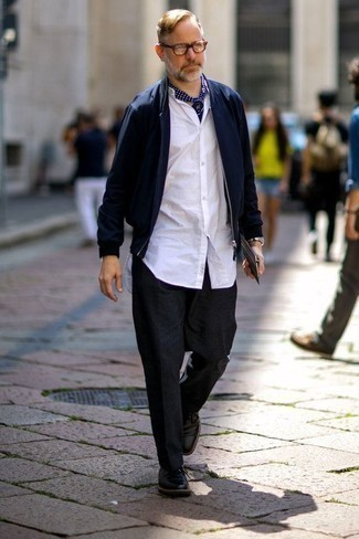 Темно-синий бомбер: с чем носить и как сочетать мужчине: Несмотря на то, что это достаточно легкий ансамбль, сочетание темно-синего бомбера и темно-серых брюк чинос приходится по вкусу стильным мужчинам, покоряя при этом сердца девушек. Любители необычных луков могут закончить ансамбль черными кожаными туфлями дерби, тем самым добавив в него немного эффектности.