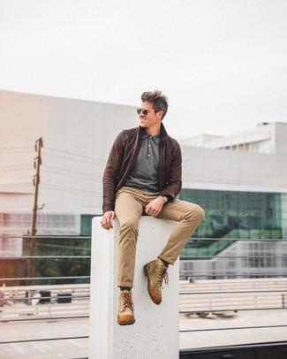 Модный лук: темно-коричневый кожаный бомбер, темно-серый свитер с воротником поло, светло-коричневые брюки чинос, светло-коричневые повседневные ботинки из плотной ткани