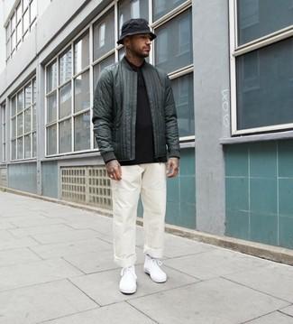 Как и с чем носить: темно-зеленый стеганый бомбер, черный свитер с воротником поло, белые брюки чинос, белые высокие кеды из плотной ткани