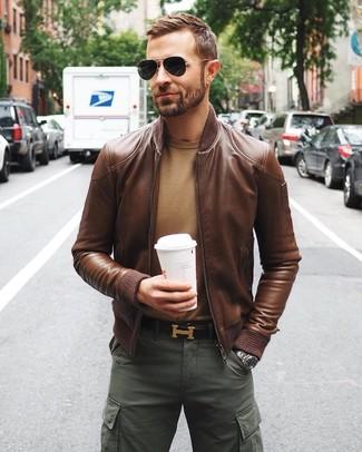 Как и с чем носить: коричневый кожаный бомбер, светло-коричневый свитер с круглым вырезом, темно-зеленые брюки карго, темно-коричневый кожаный ремень