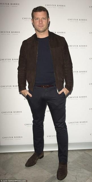Как Dermot O'Leary носит Темно-коричневый замшевый бомбер, Темно-синий свитер с круглым вырезом, Черные брюки чинос, Темно-коричневые замшевые лоферы