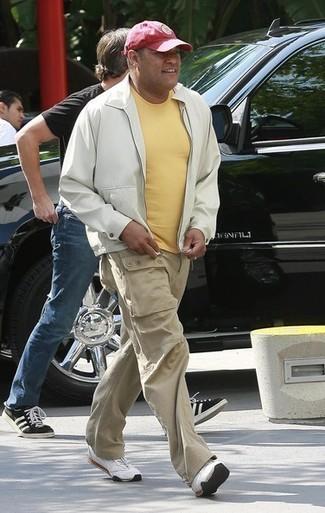 Как и с чем носить: белый бомбер, желтая футболка с круглым вырезом, бежевые брюки карго, белые кроссовки