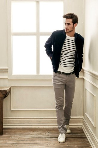 Черный замшевый бомбер и серые брюки чинос — необходимые вещи в арсенале стильного мужчины. Любители экспериментировать могут завершить образ белыми низкими кедами.