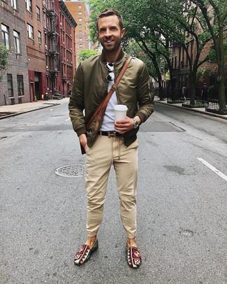 Как и с чем носить: оливковый бомбер, серая футболка с круглым вырезом, светло-коричневые брюки чинос, разноцветные слипоны из плотной ткани с принтом