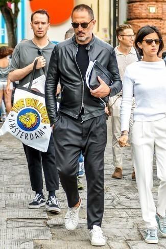 Темно-серые брюки чинос: с чем носить и как сочетать: Образ из черного кожаного бомбера и темно-серых брюк чинос поможет создать незаезженный мужской образ в расслабленном стиле. Смелые мужчины дополнят ансамбль белыми кожаными низкими кедами.