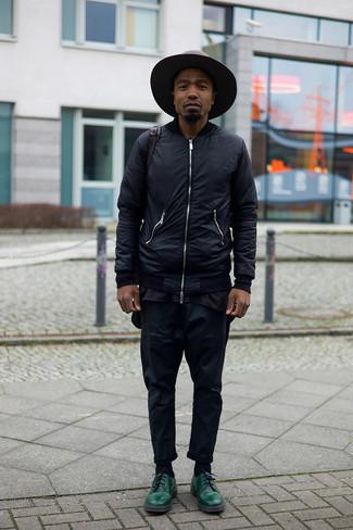 С чем носить темно-коричневую шерстяную шляпу мужчине: Если ты делаешь ставку на удобство и практичность, черный бомбер и темно-коричневая шерстяная шляпа — прекрасный выбор для стильного повседневного мужского лука. Хотел бы сделать лук немного элегантнее? Тогда в качестве обуви к этому ансамблю, стоит выбрать темно-зеленые кожаные туфли дерби.