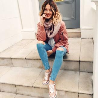 Как и с чем носить: коричневый бомбер, голубая футболка с круглым вырезом, синие рваные джинсы скинни, золотые кожаные низкие кеды